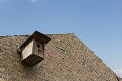 Wooden bird house on brick wall building Royalty Free Stock Images