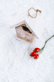 Wooden bird house christmas decoration on white snow background Royalty Free Stock Photography