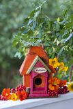 Wooden Bird House. Cute little colorful wooden bird house with welcome sign and flowers stock image
