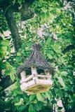 Wooden bird house hanging on green tree, analog filter. Wooden bird house hanging on the green tree. Ornithology theme. Seasonal natural scene. Analog photo stock image