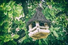 Wooden bird house hanging on green tree, analog filter. Wooden bird house hanging on the green tree. Ornithology theme. Seasonal natural scene. Analog photo stock photo