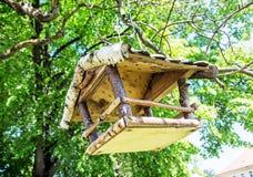 Wooden bird house hanging on the green tree. Seasonal natural scene. Ornithology theme. Detailed natural scene Royalty Free Stock Image
