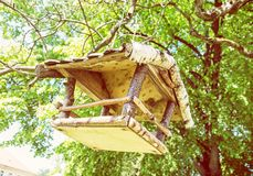 Bird house hanging on green tree, yellow filter. Wooden bird house hanging on the green tree. Seasonal natural scene. Ornithology theme. Detailed natural scene Stock Photography