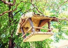 Wooden bird house hanging on green tree. Wooden bird house hanging on the green tree. Seasonal natural scene. Ornithology theme. Detailed natural scene. Retro royalty free stock photos