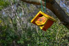 Wooden bird house hanging on a tree branch. With green foliage background royalty free stock image