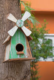 Wooden bird house with real bird nest inside, hanging on mango t Royalty Free Stock Photography