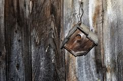 Wooden bird house. A wooden bird house sitting on an old wooden wall royalty free stock images