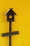 Wooden bird house with yellow wall Stock Images