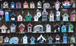 Wooden bird houses. A colorful collection of wooden bird houses on a garden fence stock photo