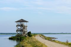 Bird observation tower in the liepaja lake. Wooden bird observation tower in the liepaja lake, road in the lake royalty free stock image