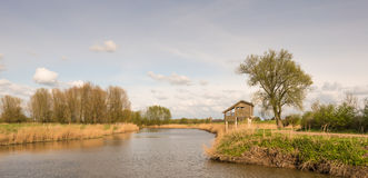 Wooden bird watching hut on concrete piles. Wooden bird observatorium at the banks of the river in a rural Dutch landscape royalty free stock image