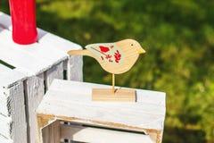 Wooden bird on white box. Wooden bird standing on the white box stock photo
