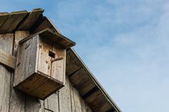 Wooden birdhouse on a wooden barn wall royalty free stock photography