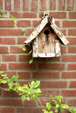 Wooden birdhouse on brick wall. Wooden birdhouse on a brick wall with some leafs Stock Photo