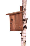 Wooden birdhouse on a stem over white Royalty Free Stock Photography
