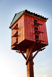 Wooden birdhouse on a wooden post in the outdoors Stock Photos
