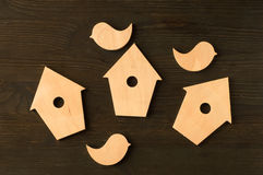 Wooden birds and birdhouses on a black wooden background Royalty Free Stock Photography