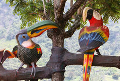 Wooden Birds in a fake tree Stock Images