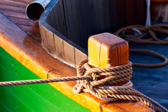 Wooden bitt with rope. Close up of wooden bitt with rope Royalty Free Stock Image