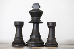 Wooden black king and rooks chess pieces. On chess board Stock Photos