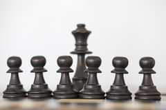Wooden black queen and pawns chess pieces. On chess board Stock Images