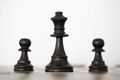 Wooden black queen and two pawns chess pieces. On chess board Royalty Free Stock Images
