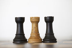 Wooden black and white rooks chess pieces. On chess board Royalty Free Stock Photos