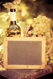 Wooden blackboard blank, wine bottle and grapes of vine Royalty Free Stock Image