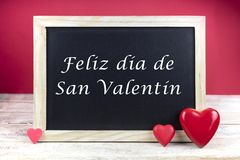 Wooden blackboard with red hearts and written sentence in Spanish Feliz dia de San Valentin, which means Happy Valentine`s day. In red background stock photos