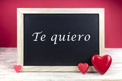 Wooden blackboard with red hearts and written sentence in Spanish Te quiero, which means I love you. In red background stock images