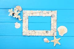 Blank frame with seashells. Wooden blank frame with seashells on blue table stock image