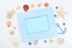Blank frame with seashells. Wooden blank frame with seashells on white table stock photos