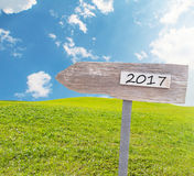 Wooden Blank Sign With Text 2017  Over Green Grass field with Cl. Oudy Blue Sky , Image for New year 2017 Concept Royalty Free Stock Images
