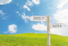 Wooden Blank Sign With Text 2017 Over Green Grass field with Clo. Udy Blue Sky , Image for New year 2017 Concept Royalty Free Stock Images