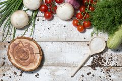 On a wooden bleached tabletop lies a set of vegetables for cooking. On a photograph on a wooden table painted in white paint lie a set of vegetables for cooking royalty free stock images