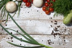 On a wooden bleached tabletop lies a set of vegetables for cooking. On a photograph on a wooden table painted in white paint lie a set of vegetables for cooking stock photo