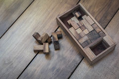 Wooden Block Brain Teaser Puzzle on Wood Background Top View royalty free stock photography