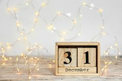 Wooden block calendar and electric garland. On table. Christmas countdown royalty free stock photo