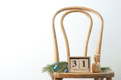 Wooden block calendar and decor on chair. Christmas countdown. Wooden block calendar and festive decor on chair. Christmas countdown royalty free stock photography