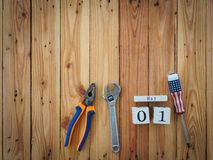 Wooden block calendar 1 May and Joinery tools on a wooden table royalty free stock image