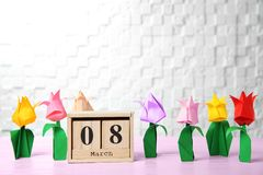 Wooden block calendar and paper tulips on table. Composition for International Women's Day Royalty Free Stock Image
