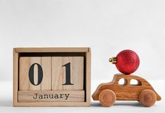 Wooden block calendar, toy car and decor on light background. Christmas countdown. Wooden block calendar, toy car and ball on light background. Christmas royalty free stock image