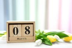 Wooden block calendar and tulips on table. Composition for International Women\'s Day Stock Photography