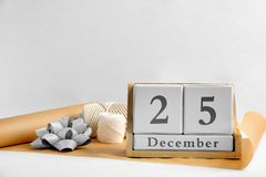 Wooden block calendar and wrapping supplies on light background. Christmas countdown. Wooden block calendar and wrapping supplies for gift on light background royalty free stock photos