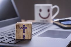 Good morning text on laptop. Wooden block with Good morning text on laptop keyboard with happy face mug background royalty free stock image