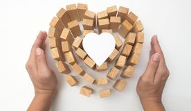 Wooden block heart and hand hold with heart paper concept. Protection your love on white background Royalty Free Stock Photo