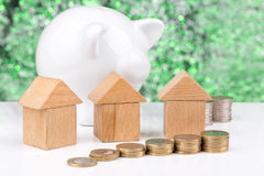 Wooden block houses, money and piggy bank: green investment Royalty Free Stock Photo