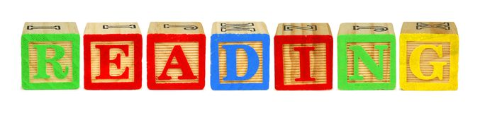 Wooden block letters spelling READING over white Stock Images