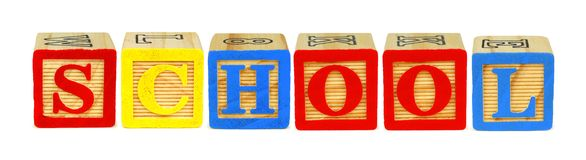 Wooden block letters spelling SCHOOL over white. Wooden toy letter blocks spelling SCHOOL isolated on white stock images