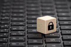 Wooden block with lock graphic on laptop keyboard. Computer security concept. Stock Photo